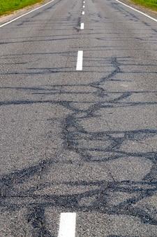 Coberta por uma rede de fendas de asfalto em estrada, a avaria foi parcialmente reparada
