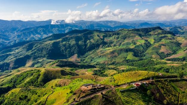 Cobertas de montanha de alto ângulo vista e caminho de estrada com resumo de plano de fundo de céu azul na temporada de chuva