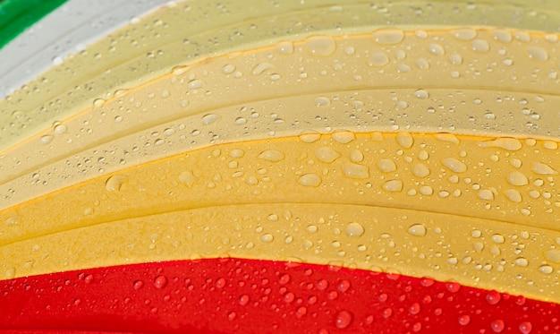 Coberto com pequenas e grandes gotas de água, um guarda-chuva de qualidade que protege da precipitação, chuva lá fora