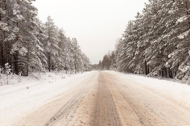 Coberto de neve e gelo e estrada de terra no inverno