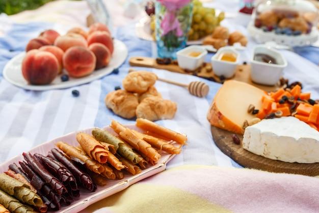 Cobertor de piquenique de verão com comida saborosa e lanches nele. fins de semana de verão