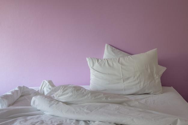 Cobertor desarrumado de rugas brancas e travesseiro em fundo rosa.