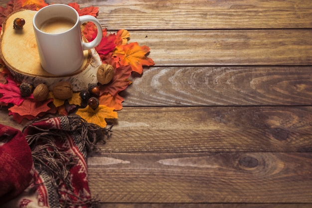 Cobertor e café perto de folhas e nozes