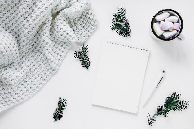 Cobertor e chocolate quente perto de galhos de coníferas e notebook