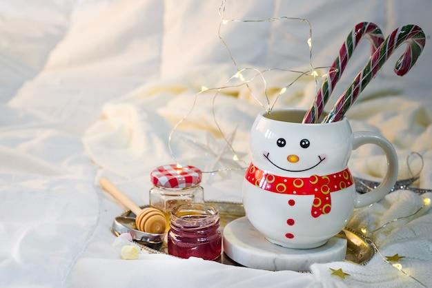 Cobertor macio acolhedor com uma taça em forma de um boneco de neve com doces de natal