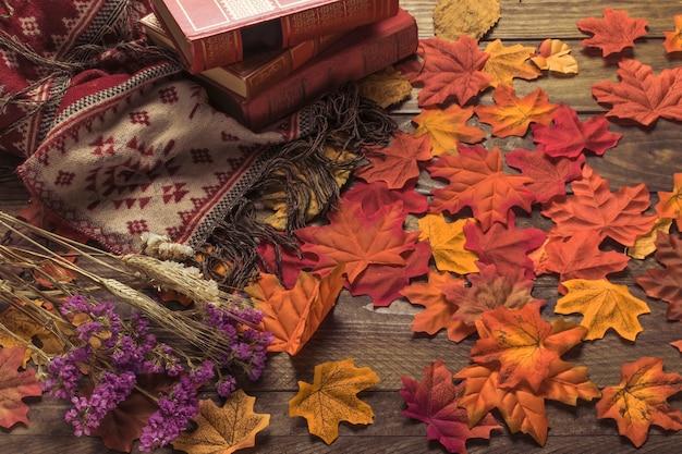 Cobertor macio e livros perto de flores e folhas