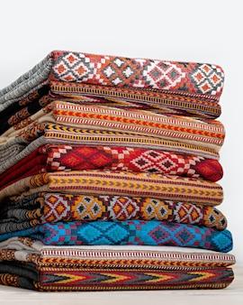 Cobertores de lã, estolas dobradas e empilhadas em várias fileiras. a textura e as cores bonitas dos produtos criam efeitos surpreendentes.