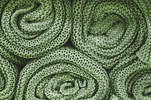 Cobertores de malha verdes enrolados em rolos