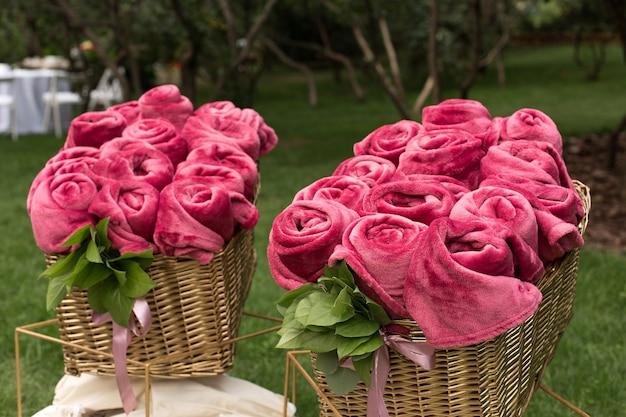 Cobertores rosa quentes enrolados em forma de rosas em uma grande cesta para convidados em uma festa de casamento ao ar livre
