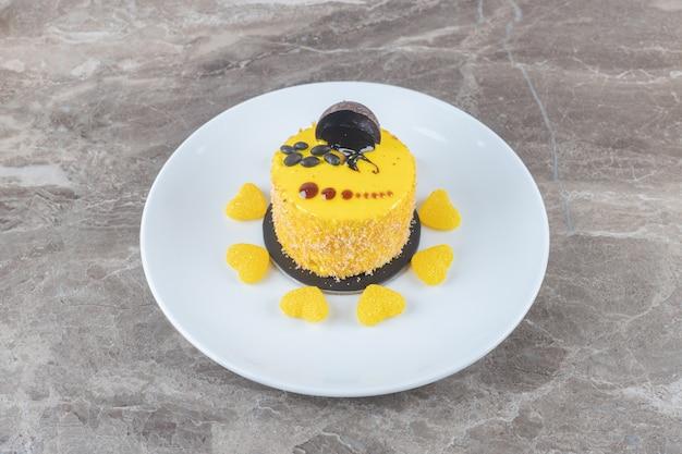 Cobertura com sabor de limão em um pequeno bolo cercado por doces de geléia em uma bandeja na superfície de mármore