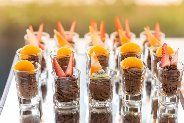 Cobertura de chocolate alce com frutas frescas e bolo de manteiga no buffet de linha