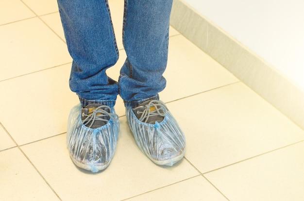 Coberturas de sapato em sapatos, no chão.