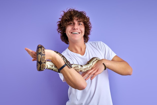Cobra python enrolada na mão do homem, cara alegre gosta, gosta de animais exóticos