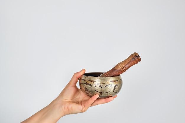 Cobre cantando tigela e vara de madeira na mão feminina