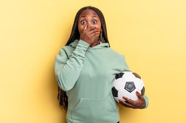 Cobrindo a boca com as mãos com uma expressão chocada e surpresa, mantendo um segredo ou dizendo oops. conceito de futebol