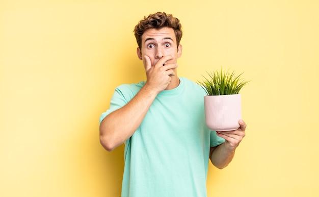 Cobrindo a boca com as mãos com uma expressão chocada e surpresa, mantendo um segredo ou dizendo oops. conceito de planta decorativa