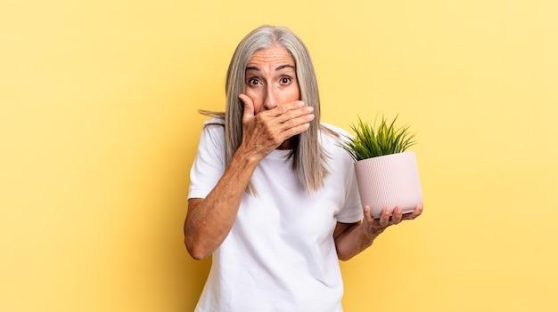 Cobrindo a boca com as mãos com uma expressão chocada e surpresa, mantendo um segredo ou dizendo oops segurando uma planta decorativa