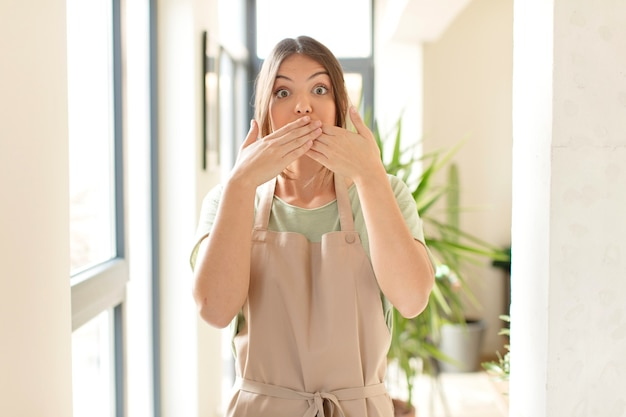 Cobrindo a boca com as mãos com uma expressão chocada e surpresa, mantendo um segredo ou dizendo oops