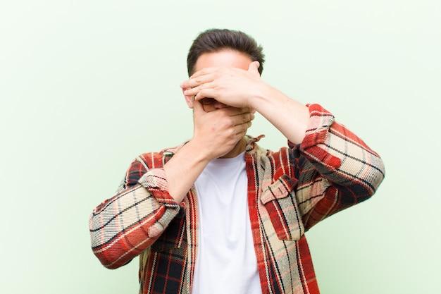 Cobrindo o rosto com as duas mãos, dizendo não à câmera! recusando fotos ou proibindo fotos