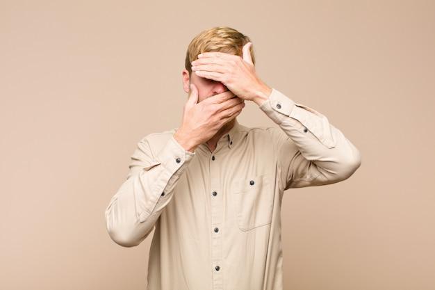 Cobrindo o rosto com as duas mãos dizendo não para a câmera! recusando fotos ou proibindo fotos