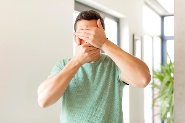 Cobrindo o rosto com as duas mãos dizendo não! recusando fotos ou proibindo fotos