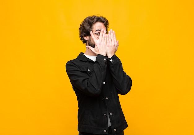 Cobrindo o rosto com as mãos, espiando entre os dedos com expressão de surpresa e olhando para o lado