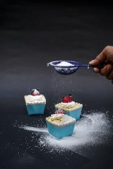 Cobrindo os cupcakes com açúcar de confeiteiro.