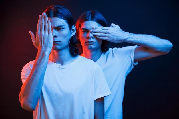 Cobrindo os olhos com as mãos. retrato de irmãos gêmeos. estúdio filmado em estúdio escuro com luz de néon.