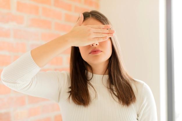 Cobrindo os olhos com uma das mãos, sentindo-se assustado ou ansioso, imaginando ou esperando cegamente por uma surpresa
