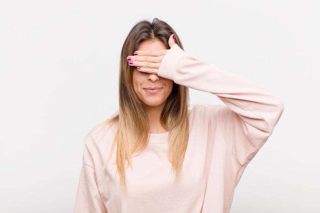 Cobrindo os olhos com uma mão sentindo medo ou ansiedade, pensando ou esperando cegamente por uma surpresa