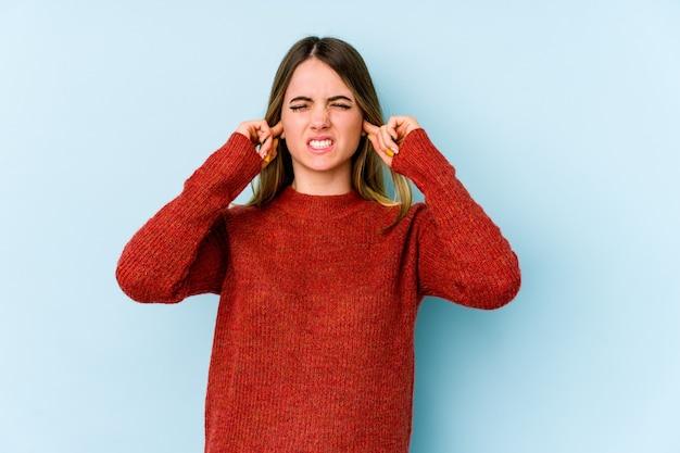 Cobrindo os ouvidos com os dedos, estressado e desesperado por um ambiente barulhento.