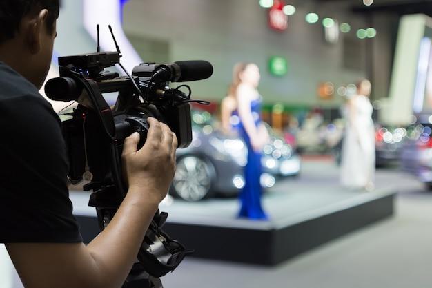 Cobrindo um evento no palco com uma câmera de vídeo.