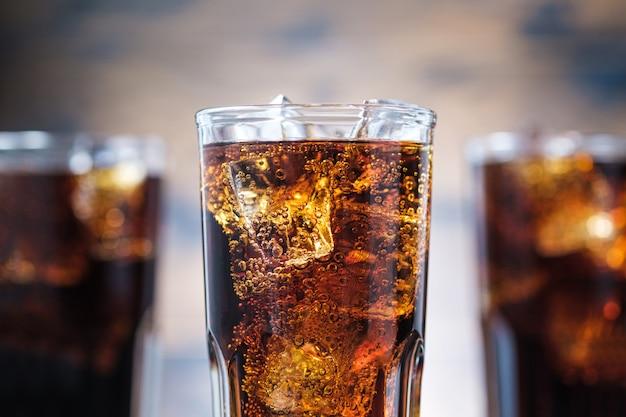 Coca-cola closeup com bolhas e cubos de gelo. bebida com gás gelada
