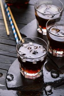 Coca-cola com cubos de gelo em copos na mesa de madeira escura
