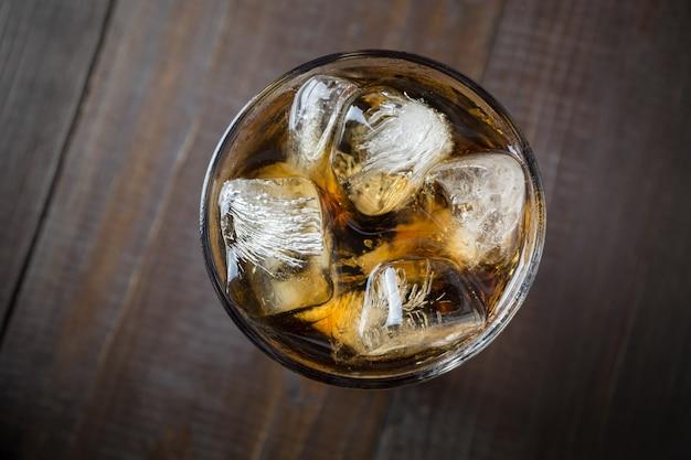 Coca-cola com cubos de gelo na placa de madeira