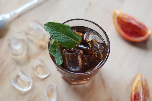 Coca-cola coquetel com gelo em um copo. em uma placa de madeira são fragmentos de frutas. vista de cima. foto com profundidade de campo.