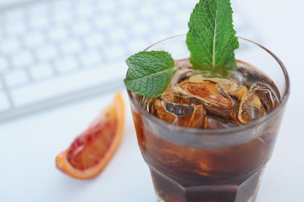 Coca-cola coquetel com gelo em um copo. fica na mesa do escritório, no teclado. vista de cima.