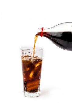 Coca-cola derramando bebida em copo com gelo no fundo branco