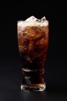 Coca-cola em copo com cubos de gelo transparentes isolados em fundo preto