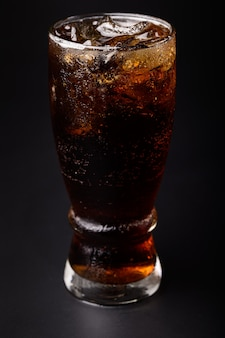 Coca-cola em vidro com cubos de gelo transparentes isolados em fundo preto