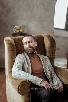 Cochilo na poltrona. conselheiro profissional vestindo um casaco de lã cinza, tirando uma soneca na poltrona enquanto se sente cansado