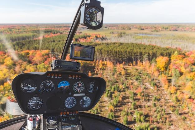 Cockpit de helicóptero em voo sobre madeira de outono