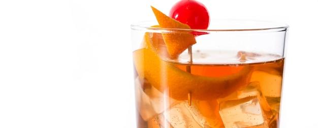 Cocktail à moda antiga com laranja e cereja isolado no branco