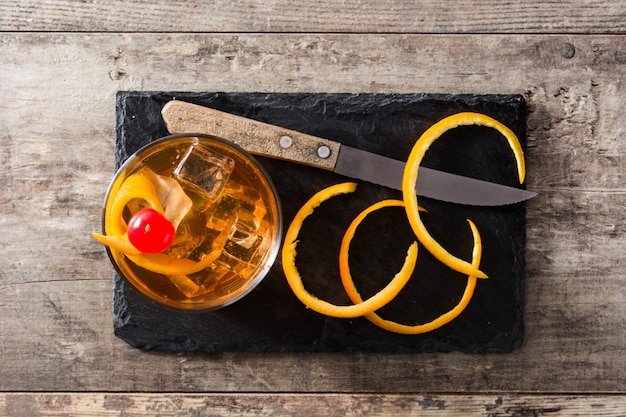 Cocktail à moda antiga com laranja e cereja na mesa de madeira, vista superior