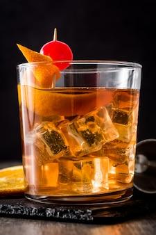 Cocktail à moda antiga com laranja e cereja na mesa de madeira