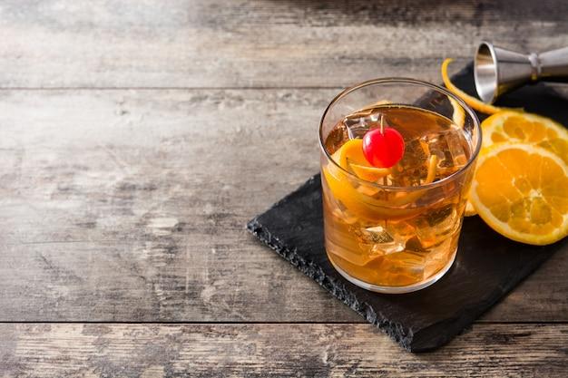 Cocktail à moda antiga com laranja e cereja no espaço da cópia de mesa de madeira