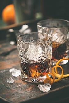 Cocktail alcoólico com casca de laranja e gelo