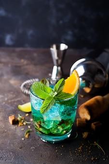 Cocktail alcoólico com sambuca, licor, suco de laranja, gelo picado e hortelã
