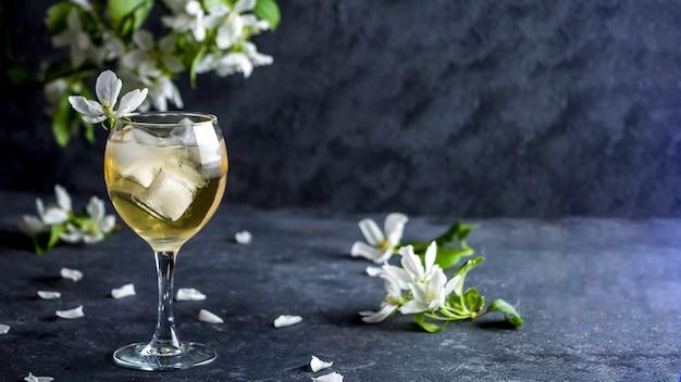 Cocktail alcoólico de maçã com vinho espumante em copo com flores