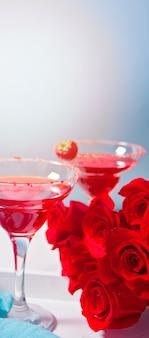 Cocktail alcoólico exótico vermelho em copos claros e rosas vermelhas na bandeja de madeira branca para jantar romântico.
